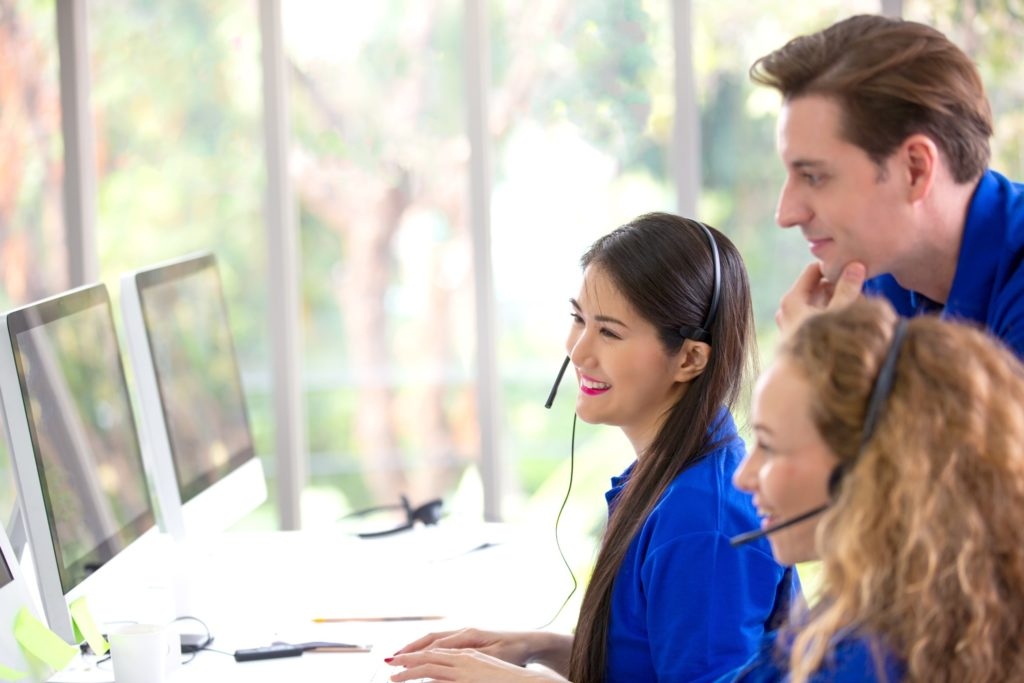 call-center-staff-in-blue-t-shirt-worker-accompanied-by-her-team-smiling-customer-support-operator